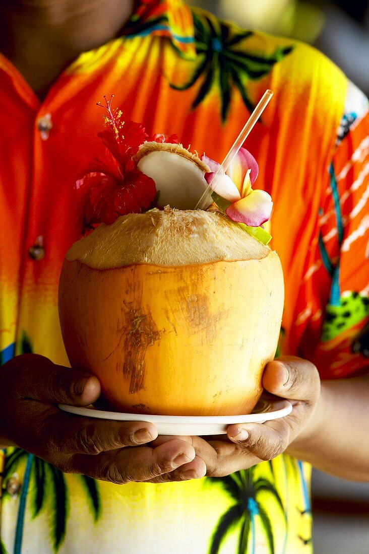 Man in colourful shirt holding a coconut drink (Seychelles)