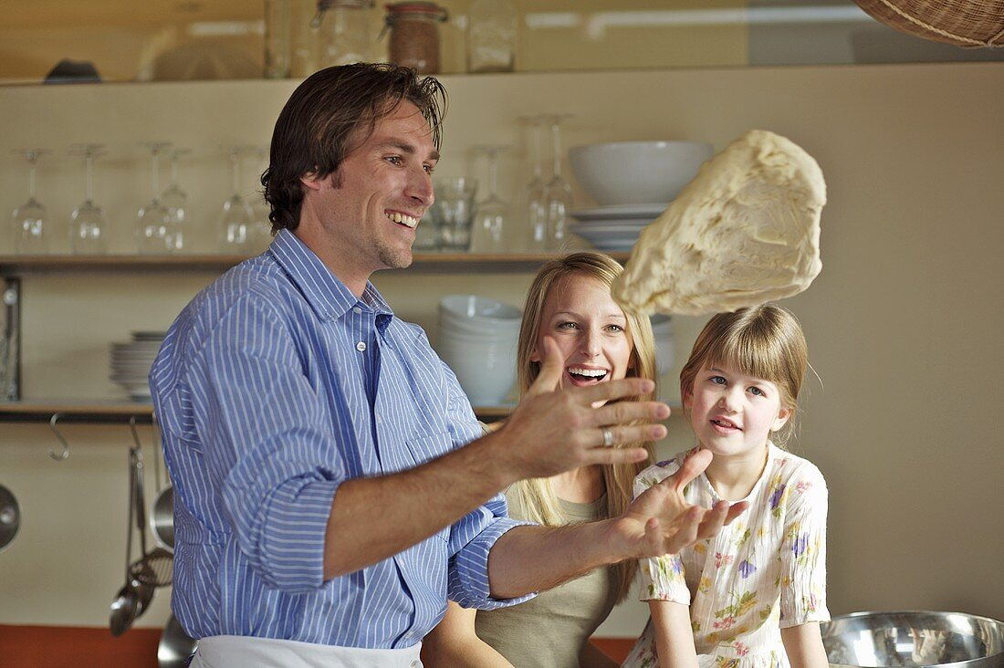 Family in kitchen, father tossing pizza dough