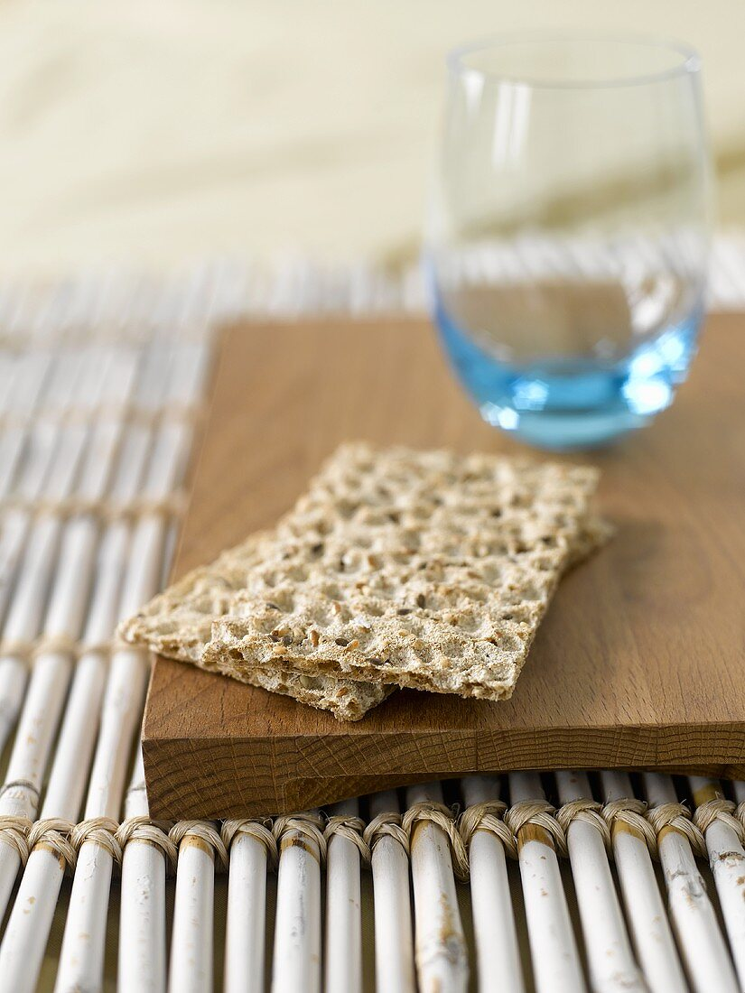 Wholemeal crispbread and tumbler on wooden board