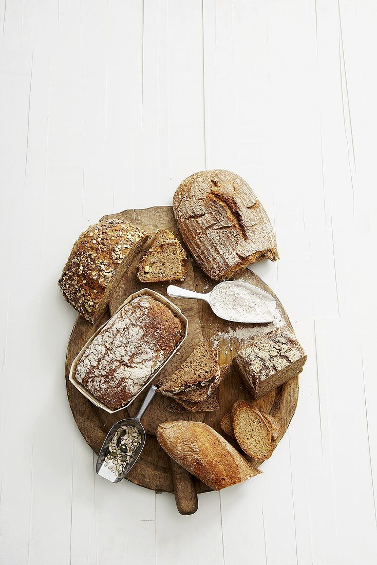 Various types of bread on wooden breadboard