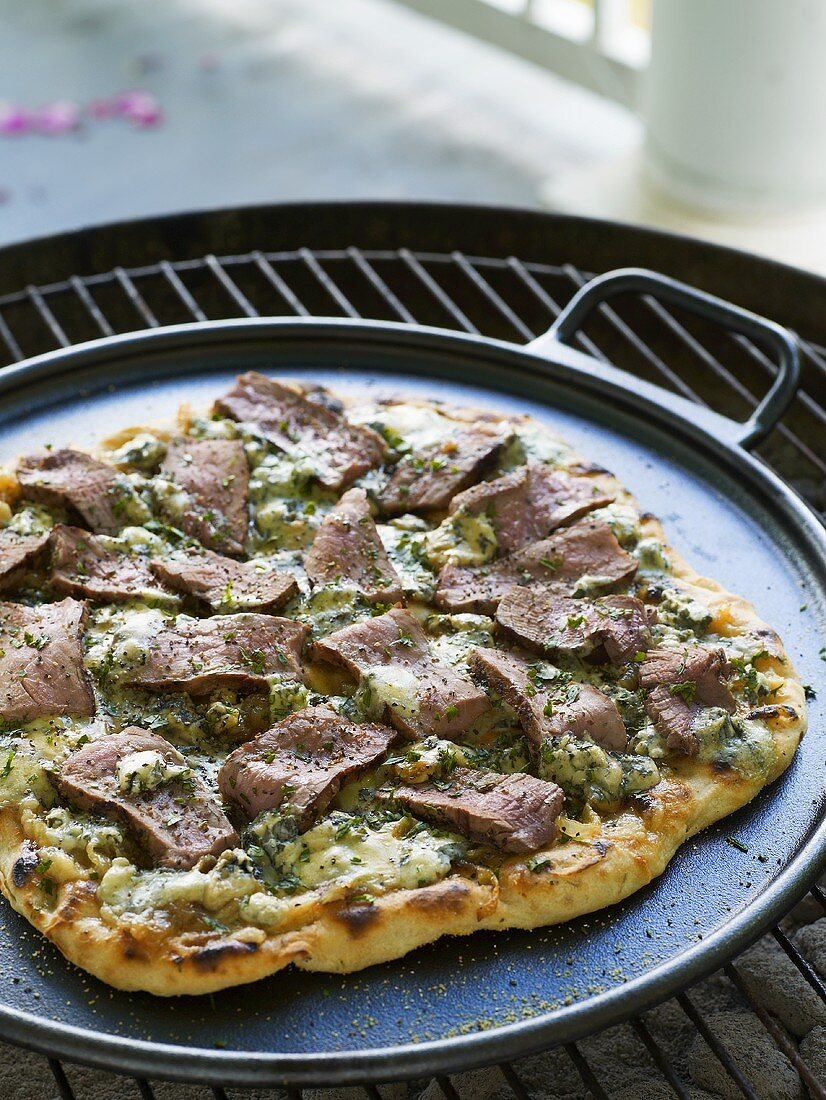 Pizza topped with beef fillet on barbecue