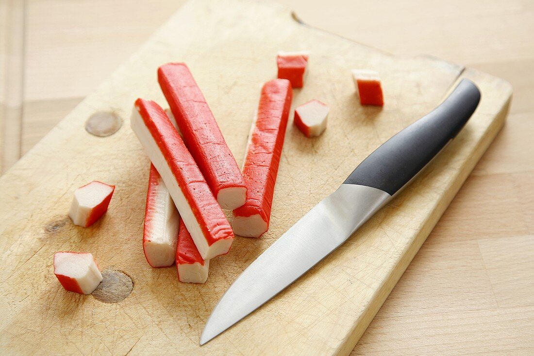Surimi with knife on chopping board