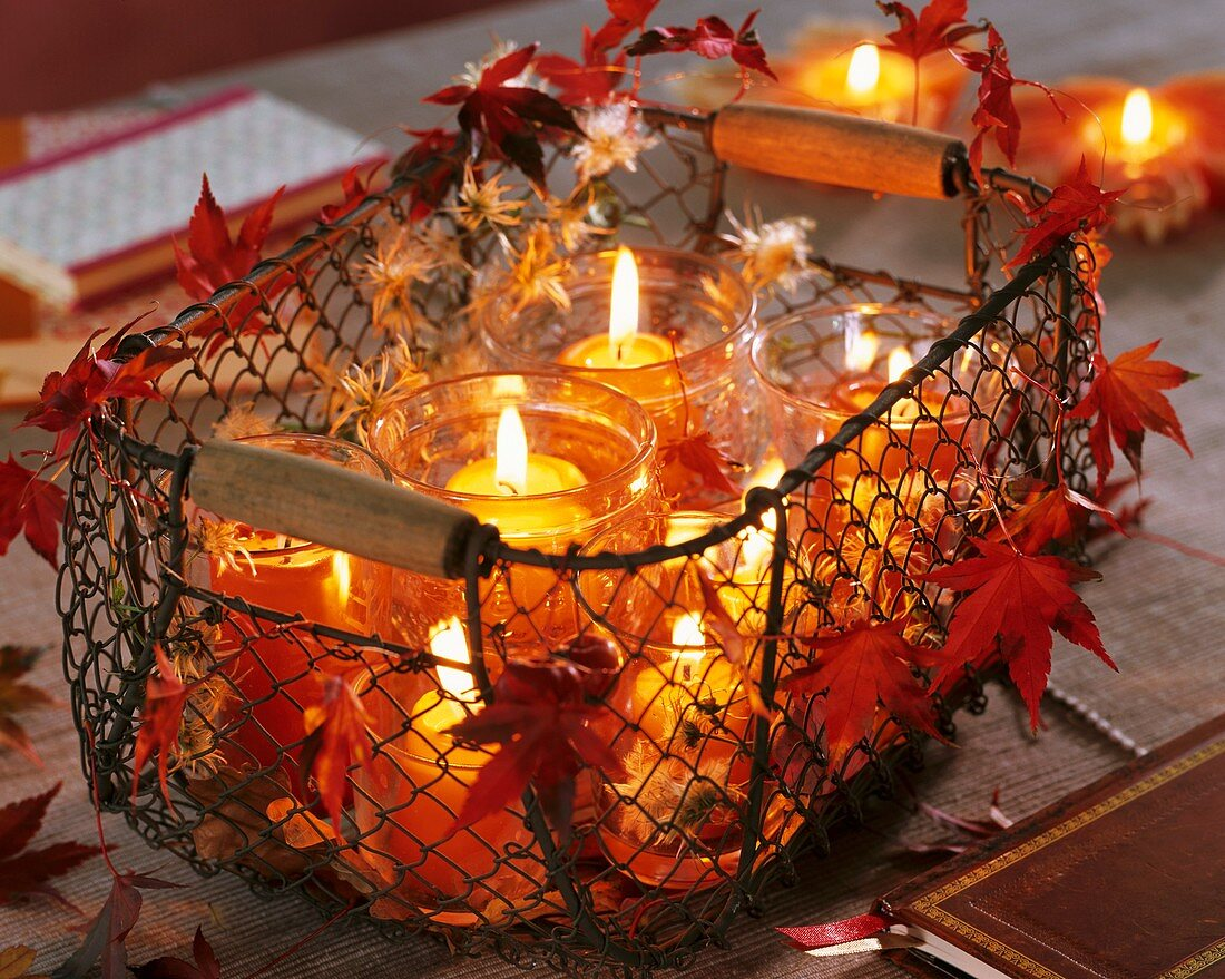 Windlights in wire basket decorated with maple leaves