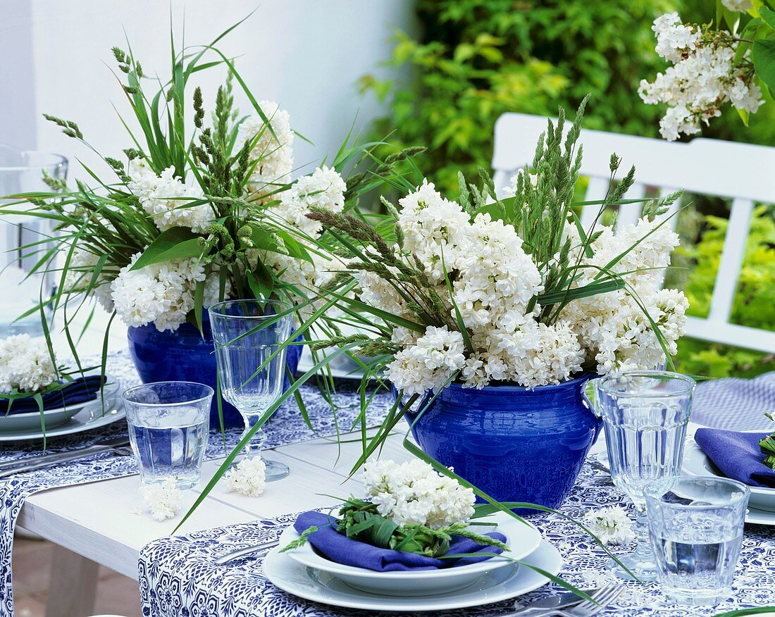 Blue and white table decorations with lilac and grasses