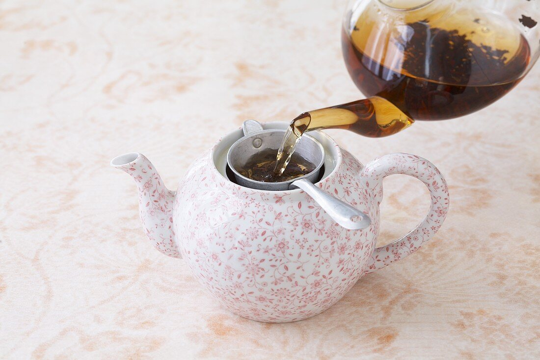 Pouring brewed tea through a strainer into a teapot