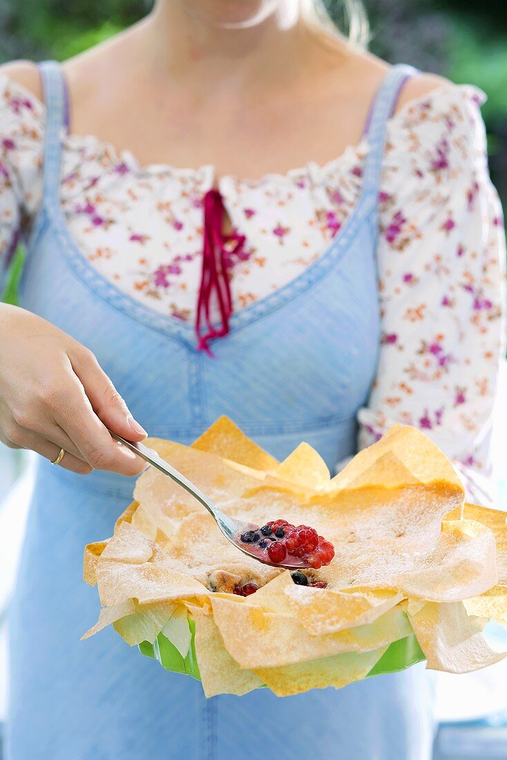 Woman holding a mixed berry pie with filo pastry