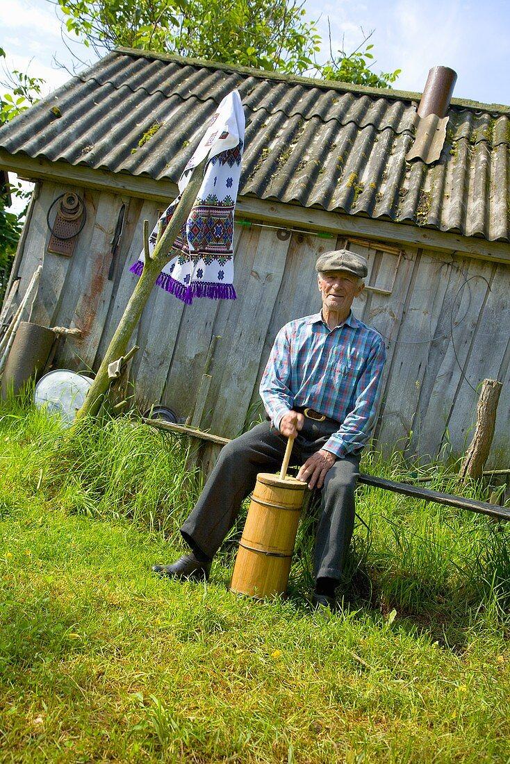 Making butter: An elderly man with butter churn