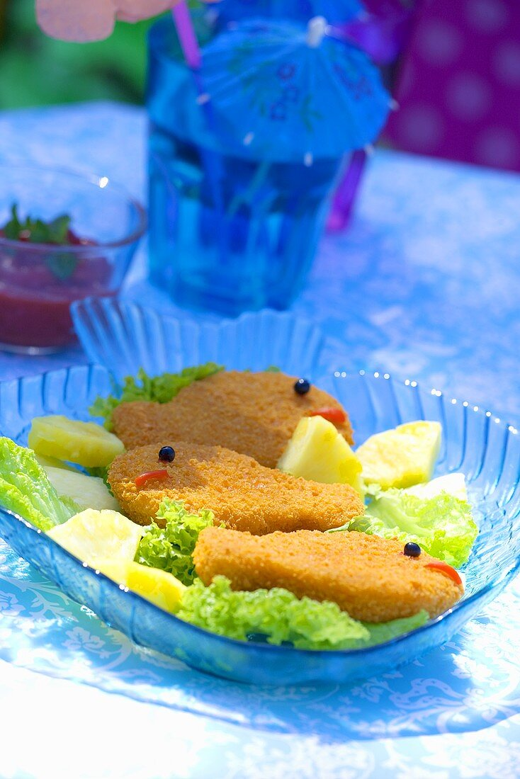 Breaded fish-shaped fish fillets with pineapple