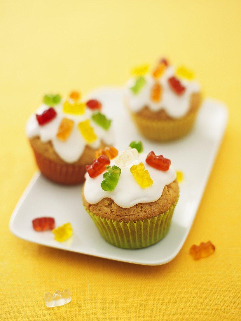 Three iced muffins with gummi bears