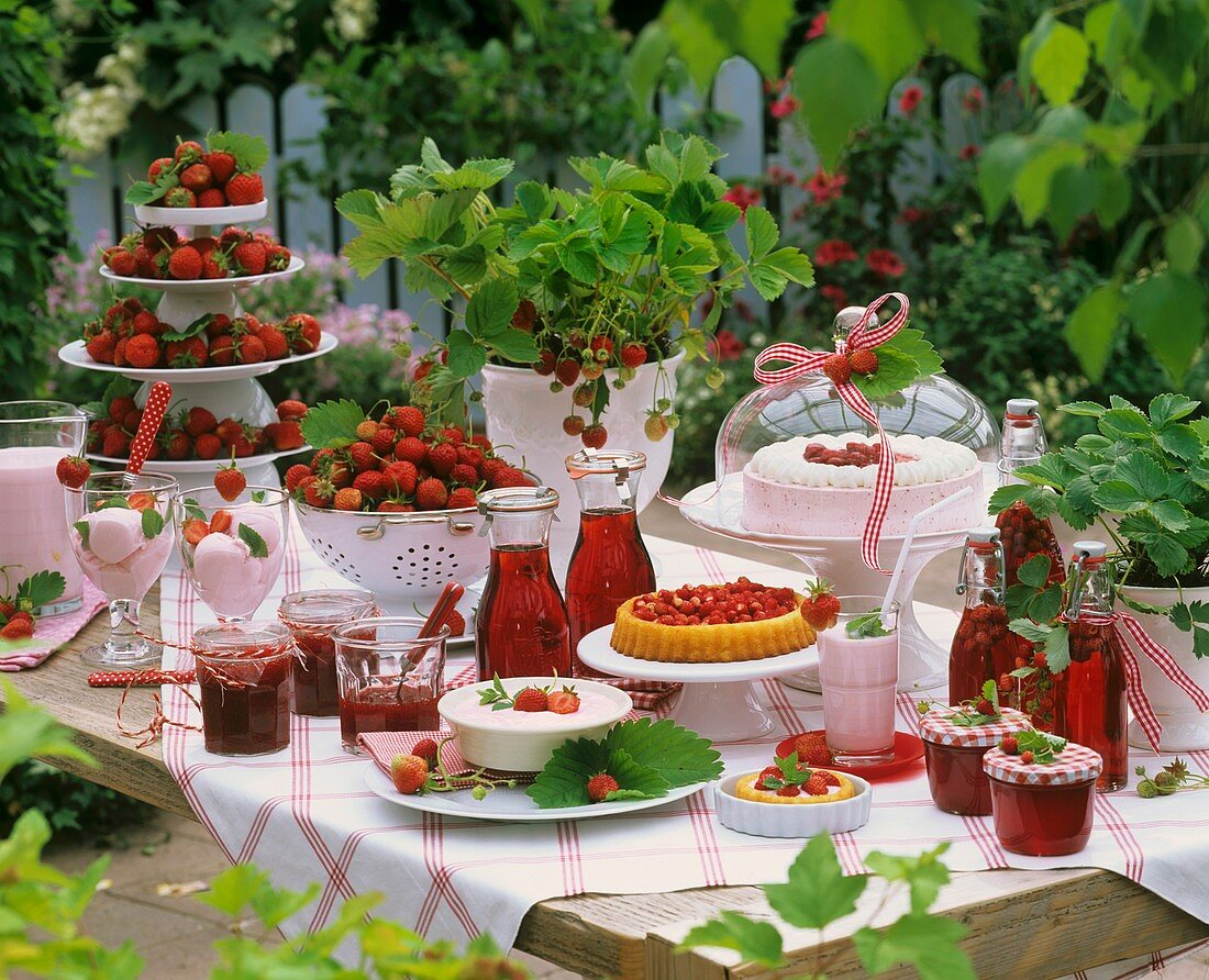 Strawberries, jam, cakes and strawberry vinegar on table