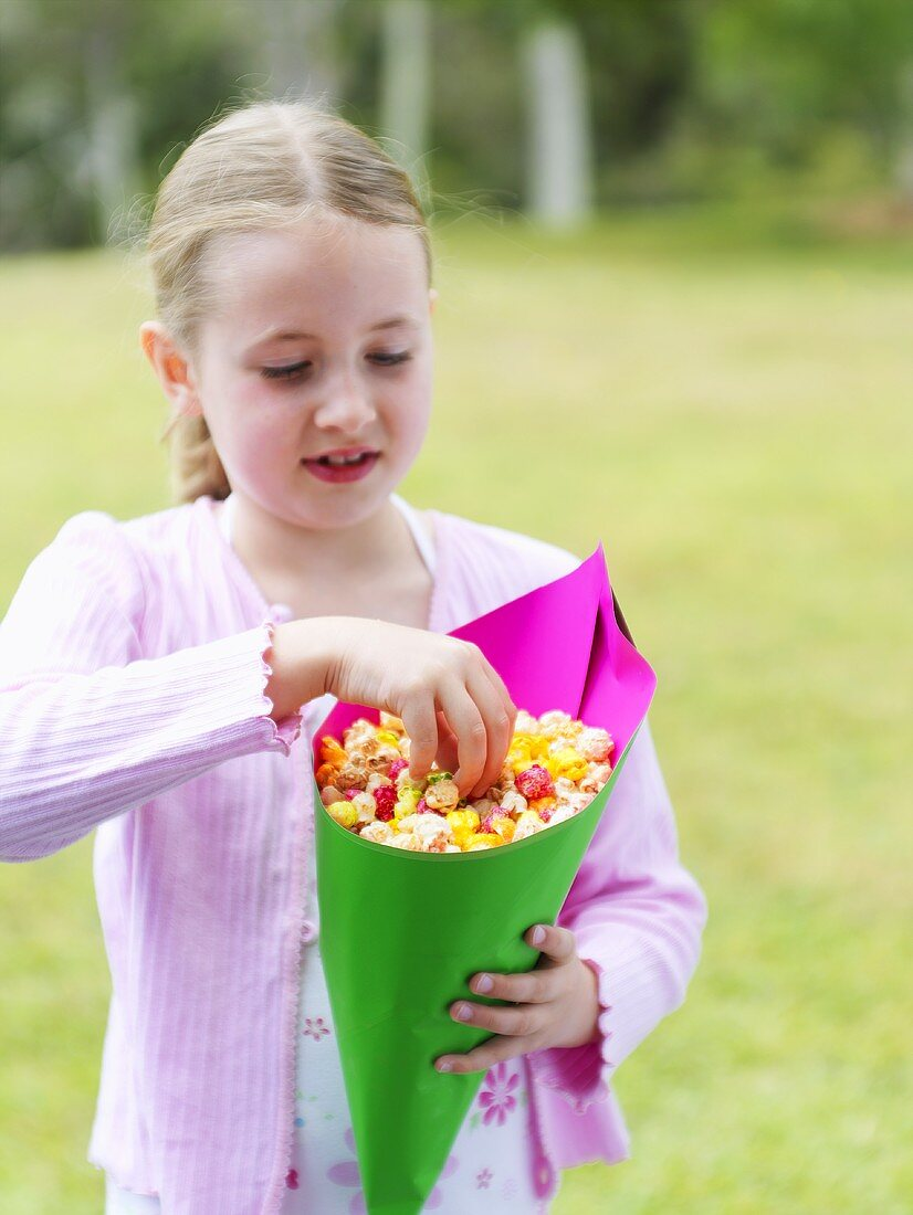 Blond girl with a cone of popcorn out of doors