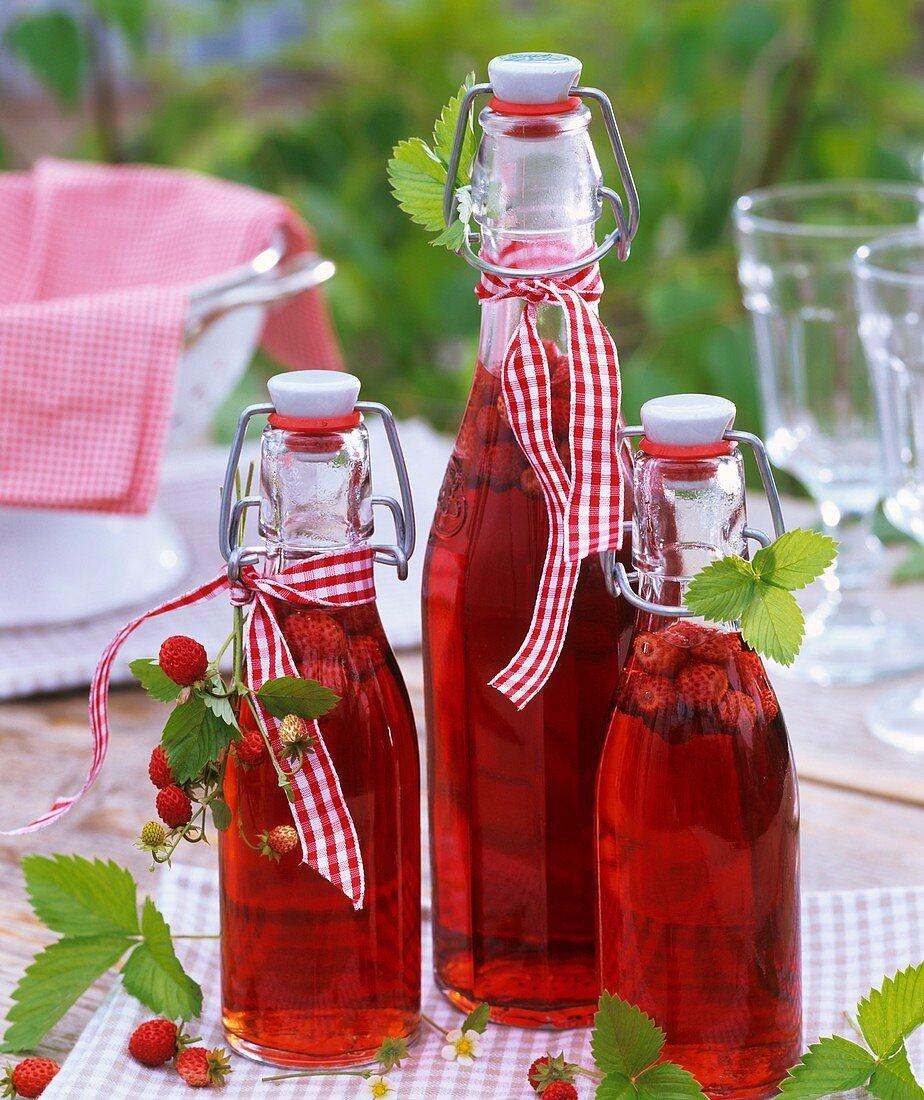 Wild strawberry vinegar decorated with fresh wild strawberries