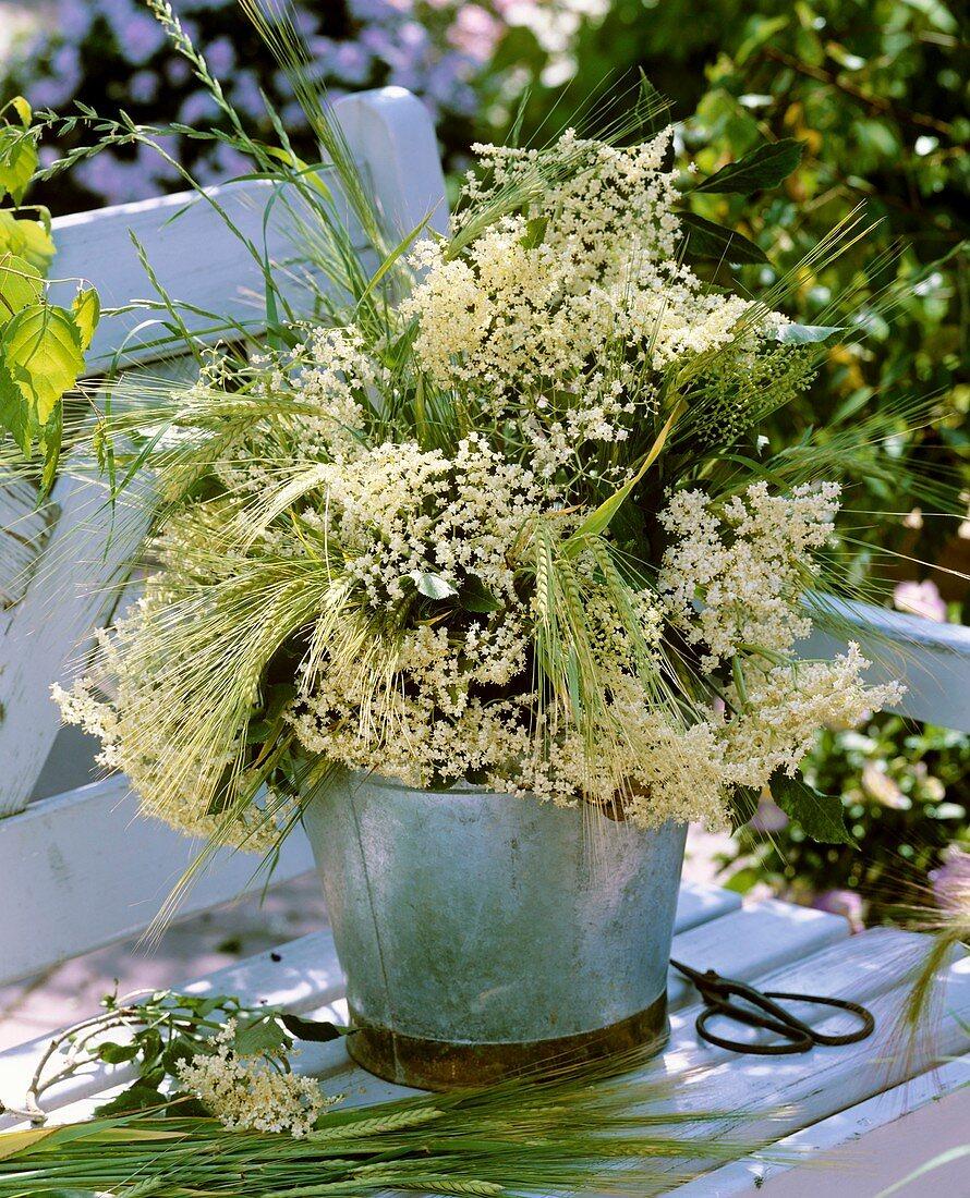 Elderflowers, barley and grasses in metal container