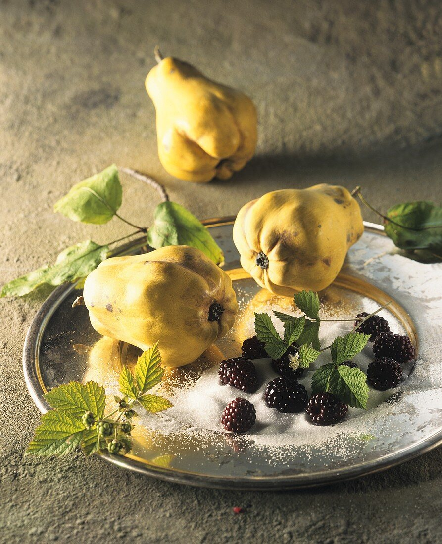 Pear-shaped quinces and blackberries with sugar on a tray