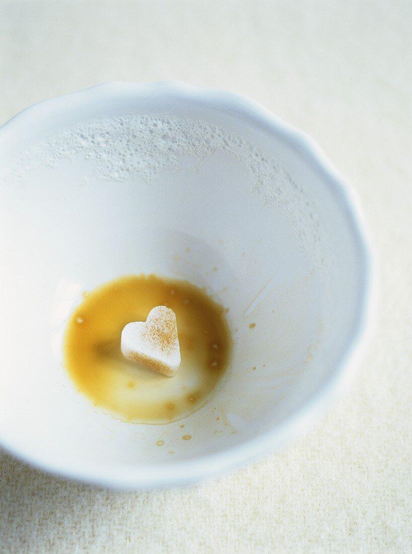 Dregs of café au lait with heart-shaped sugar lump
