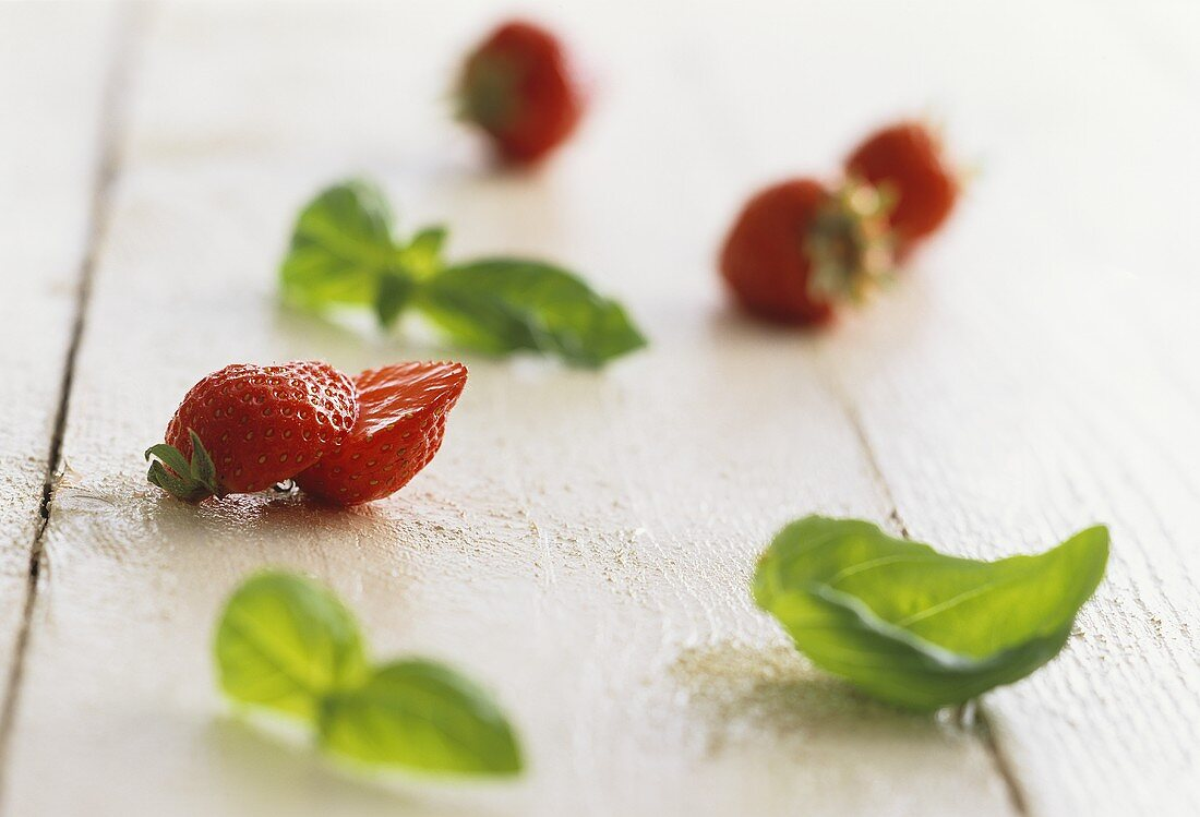 A display of strawberries and basil leaves