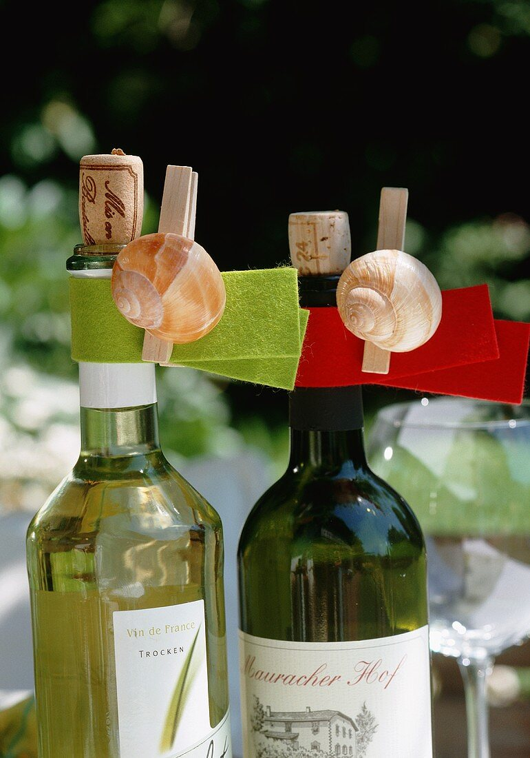 Bottles of white wine decorated with snail shells