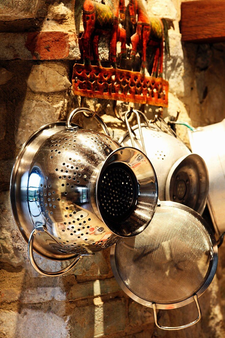 Colanders and sieves hanging on the wall in a Mediterranean kitchen, Umbria, Italy