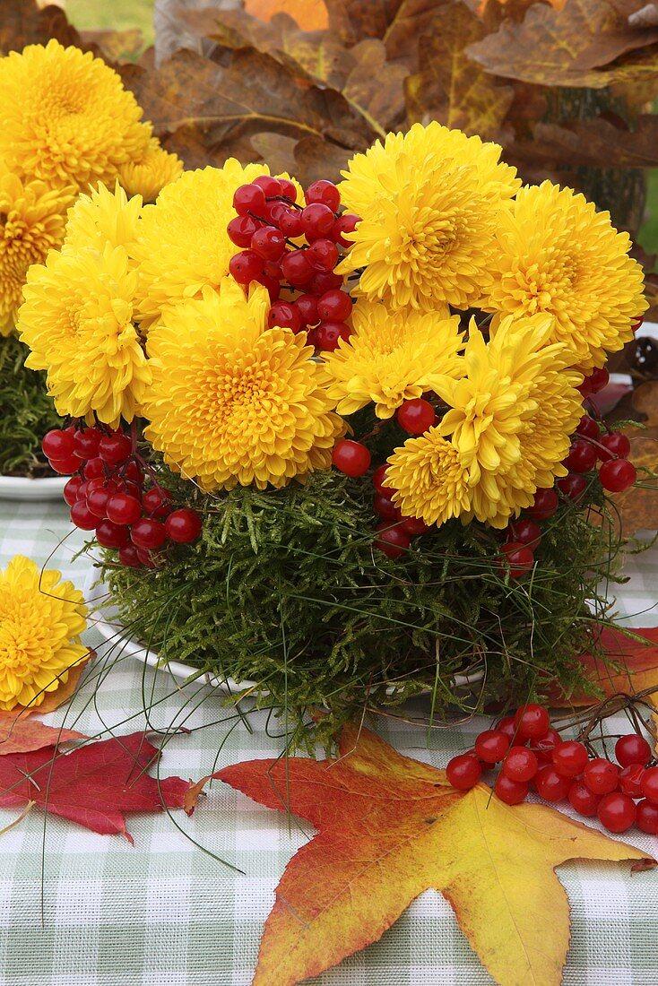 Autumnal flower arrangement of chrysanthemums, moss and berries