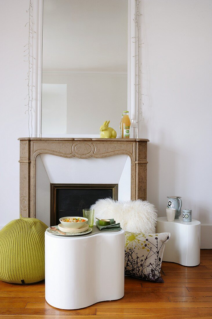 An occasional table and cushions in front of a fireplace