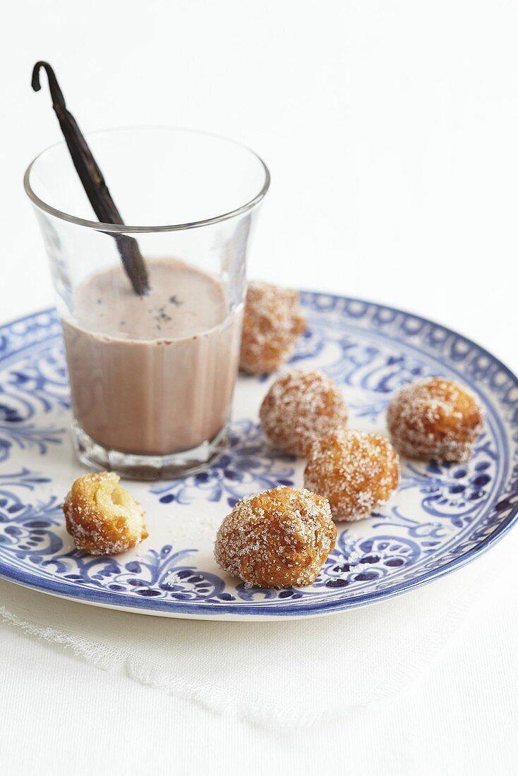 A glass of cocoa with a vanilla pod and mini doughnuts