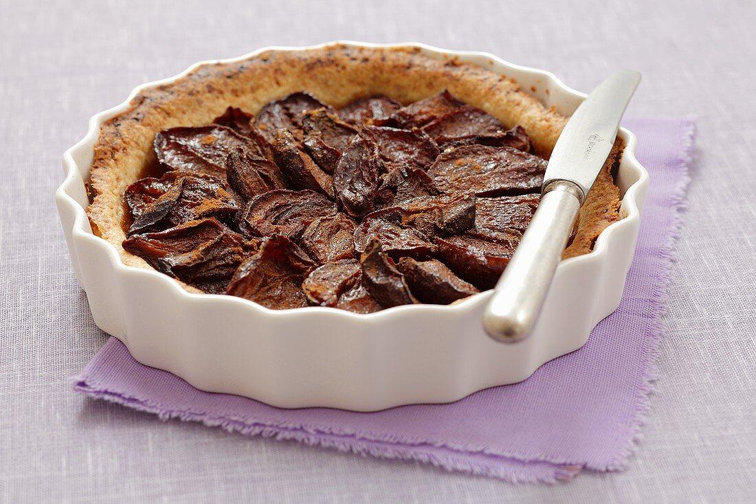 Plum tart with cinnamon in a tart dish