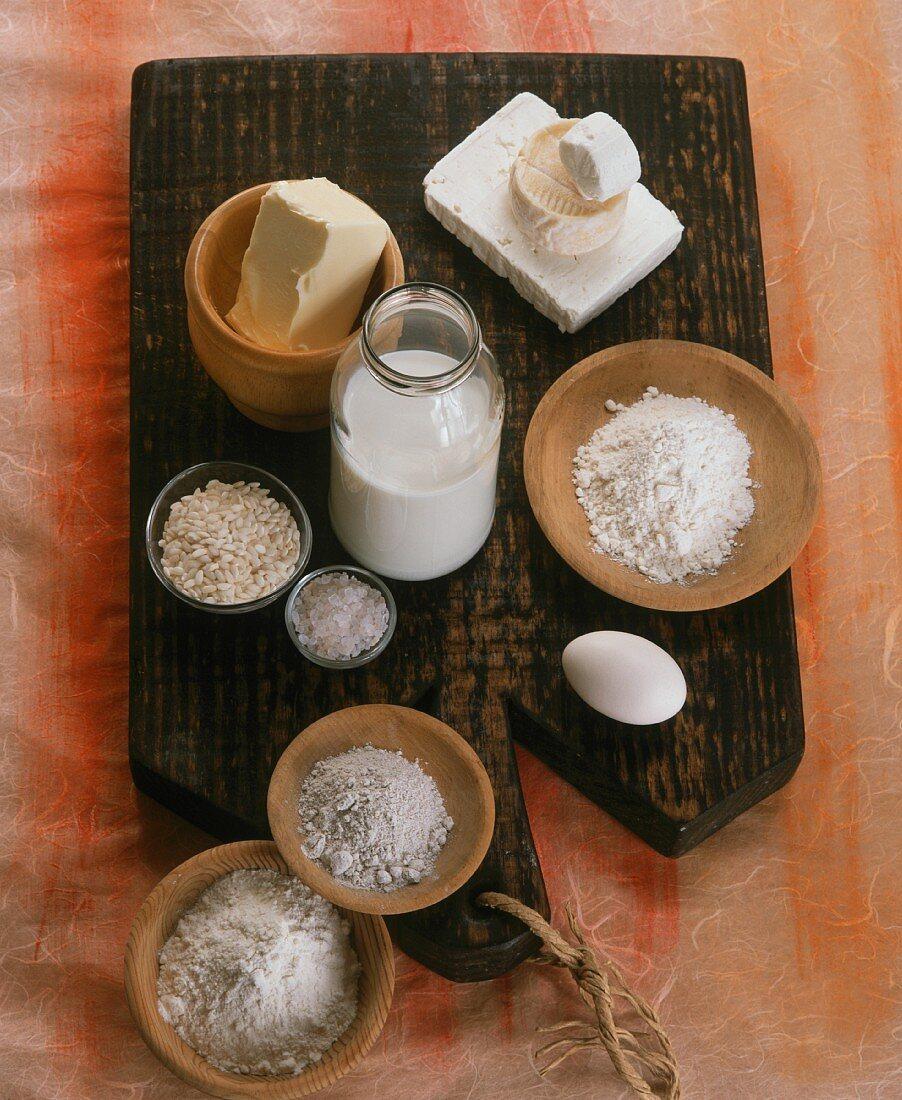 An arrangement of flour, milk, rice, cheese, eggs, sugar and butter