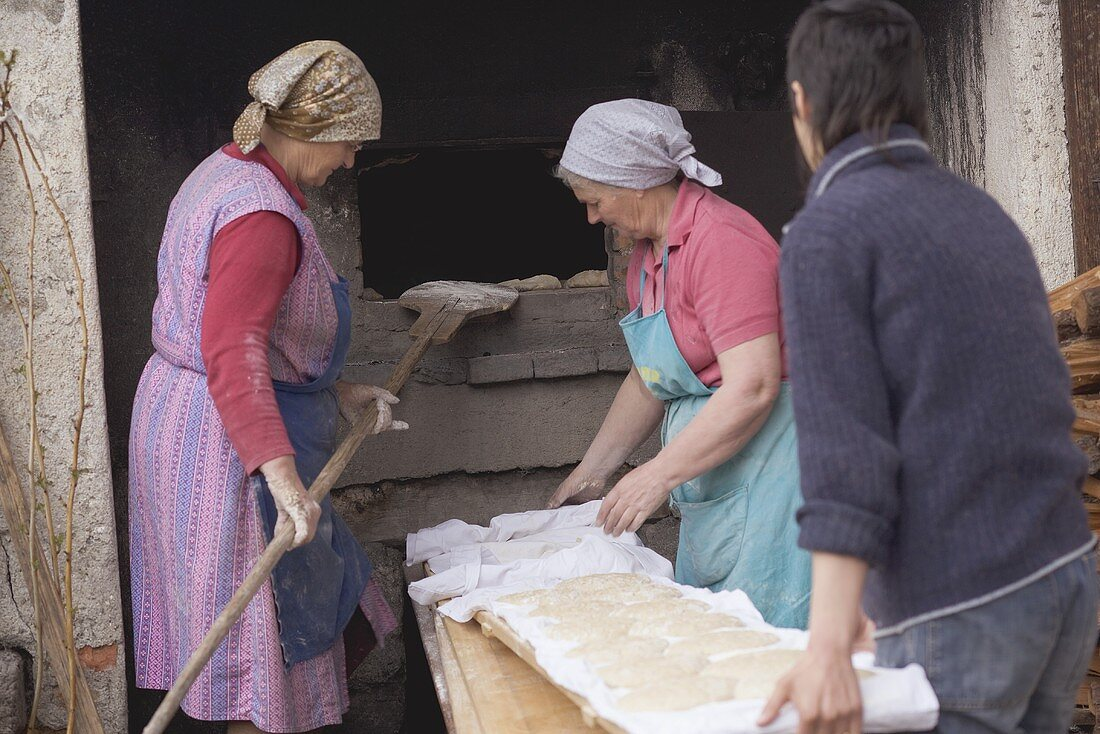 Countrywomen putting unbaked bread into old stone oven