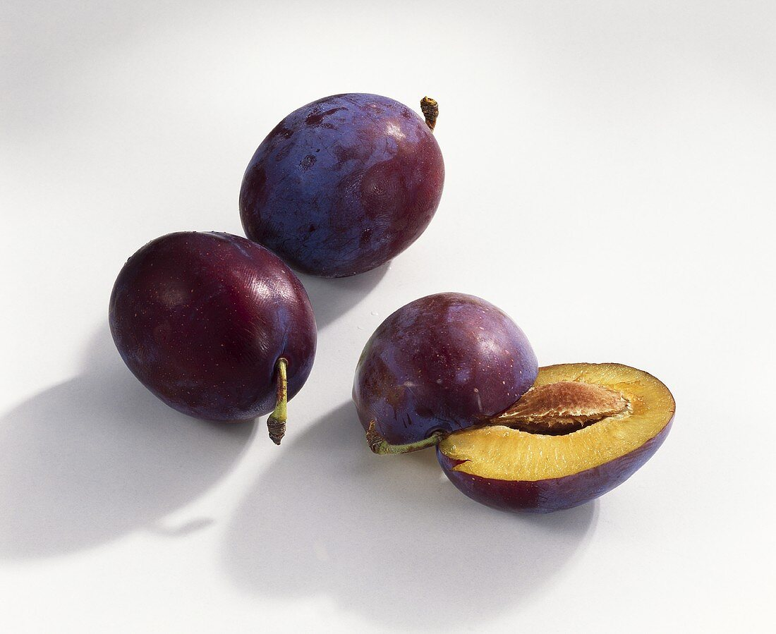 Two whole and one halved plum (variety: Top)