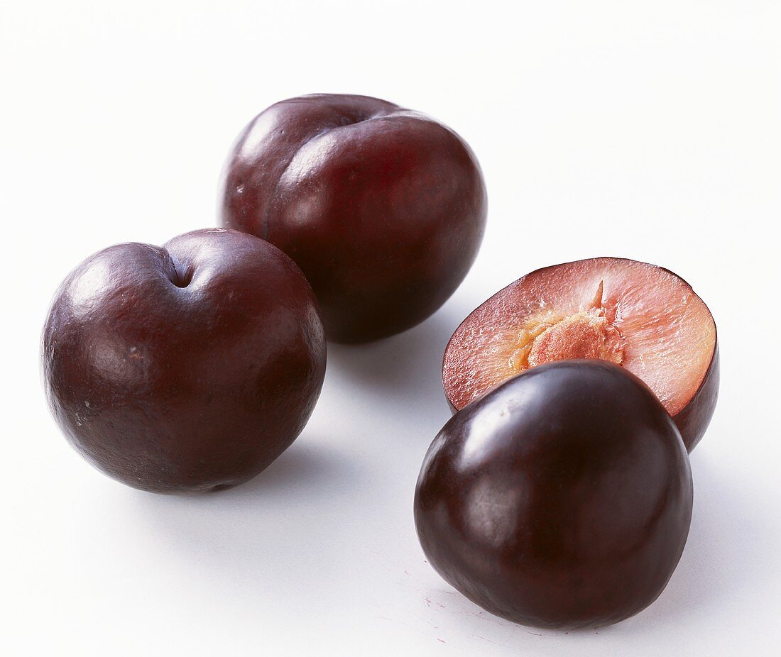 Two whole and one halved plum (variety: Angeleno)