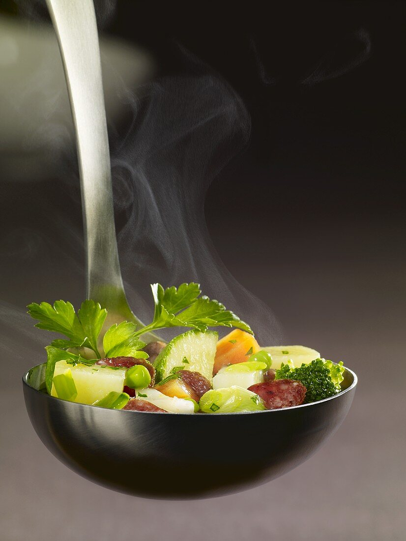 Ladle full of vegetable stew and cabanossi