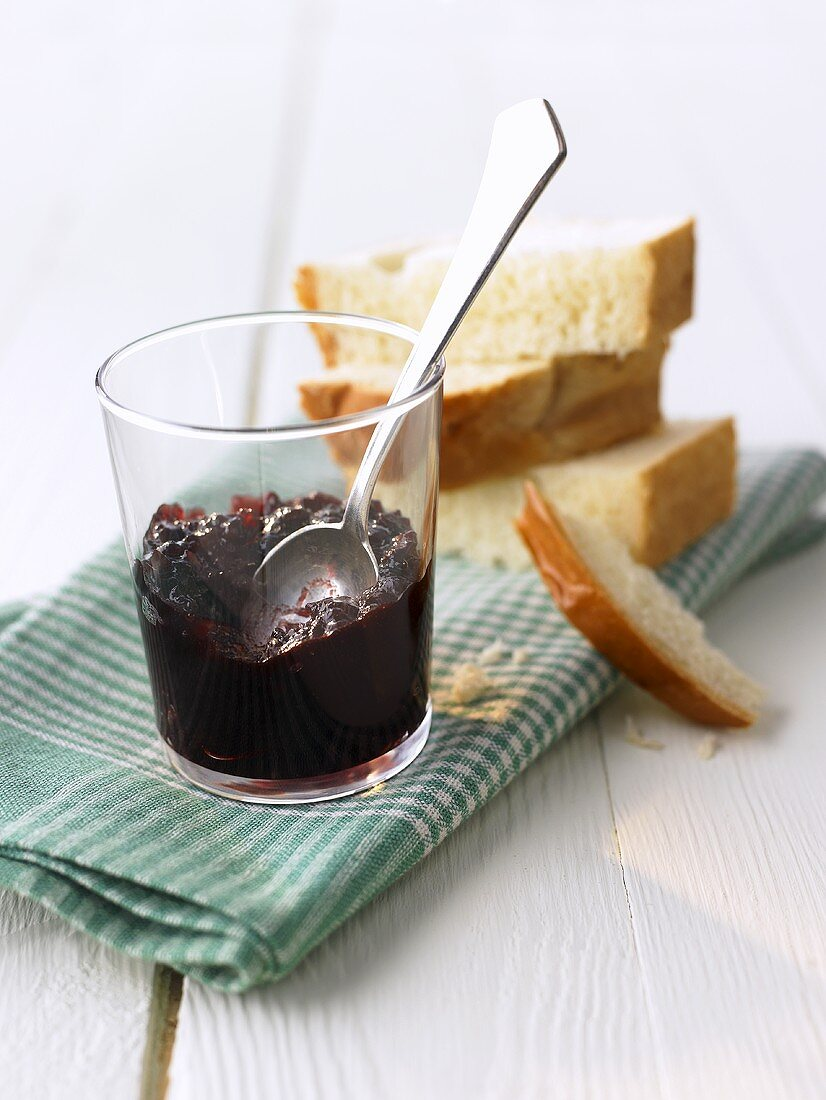 Elderberry jam in a glass, white bread