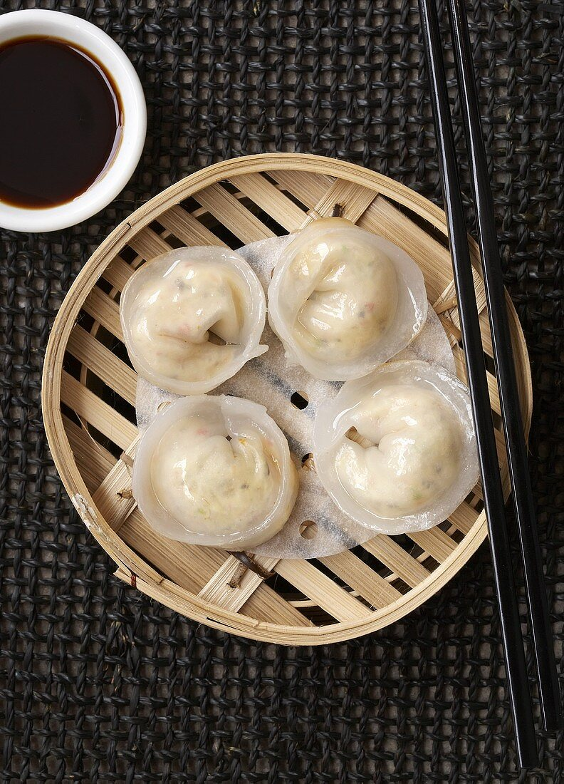 Dim sum in a bamboo basket with soy sauce