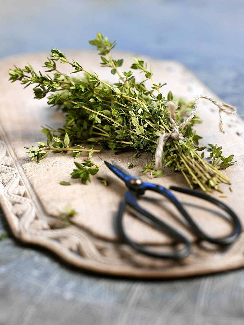 Fresh thyme with herb scissors on chopping board