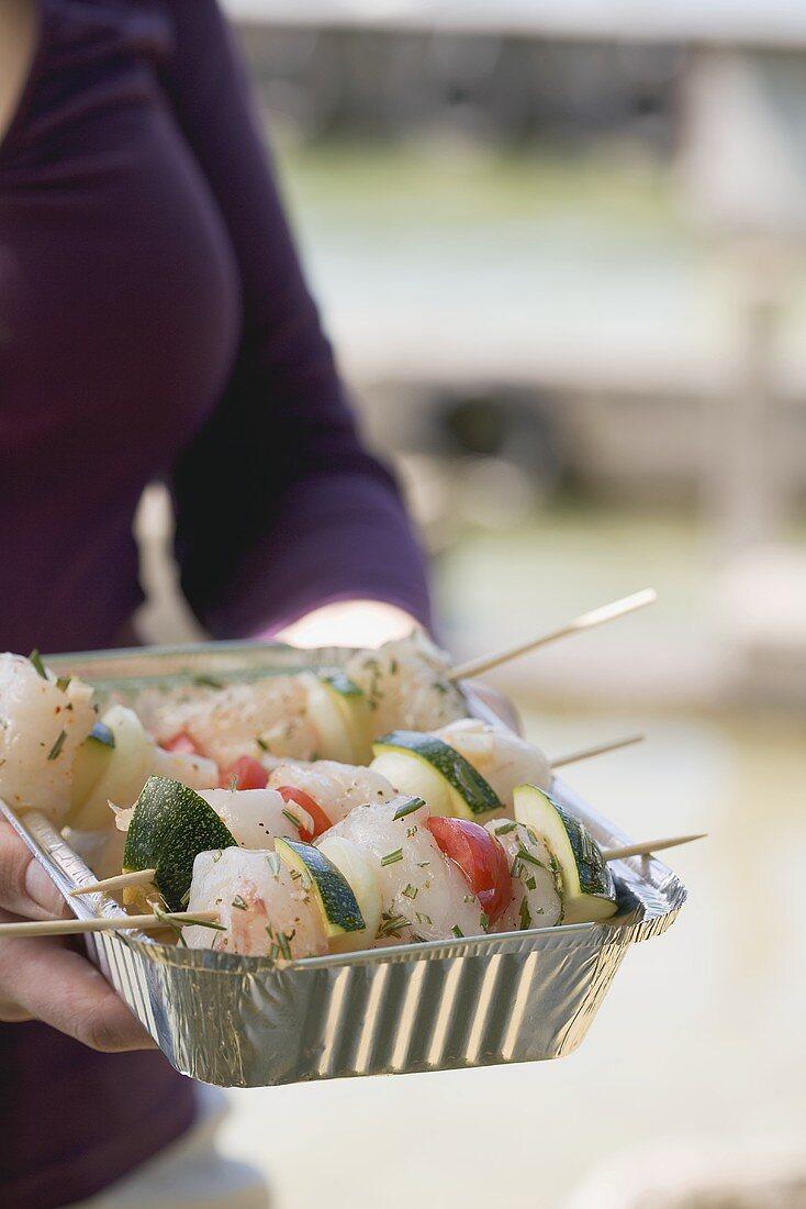 Woman holding raw fish & vegetable kebabs in aluminium dish