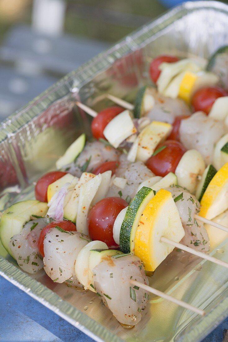 Raw fish and vegetable kebabs in aluminium dish