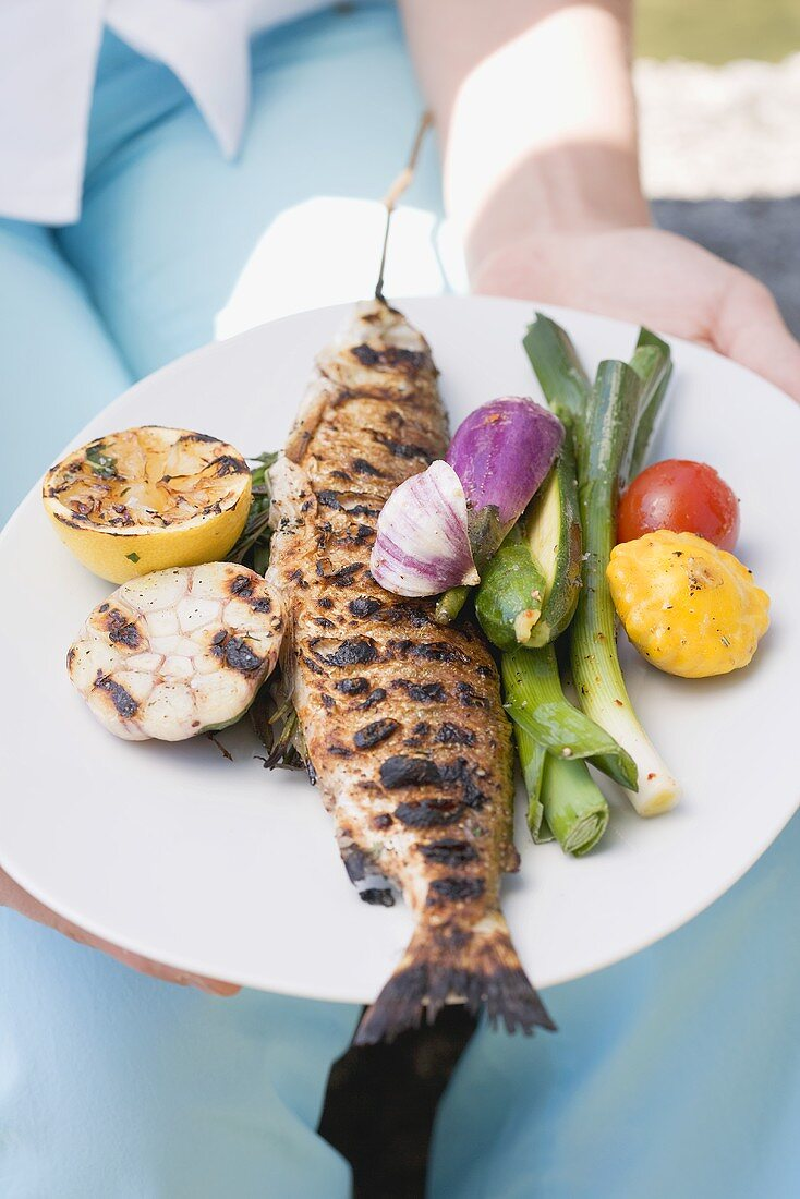 Woman holding plate of grilled fish and vegetables