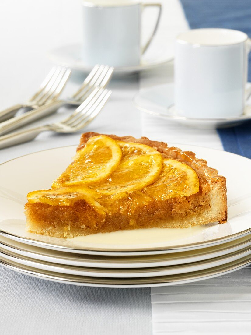 A piece of orange and almond tart on a pile of plates