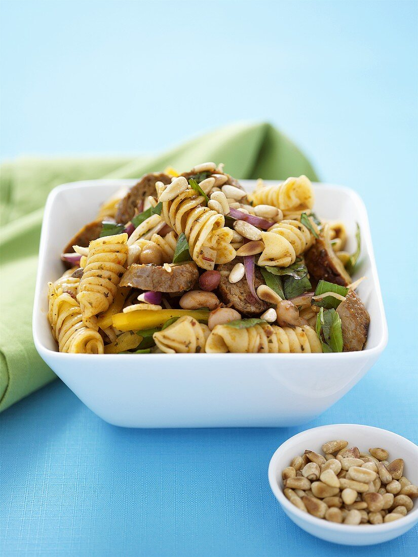 Pasta and sausage salad with pine nuts