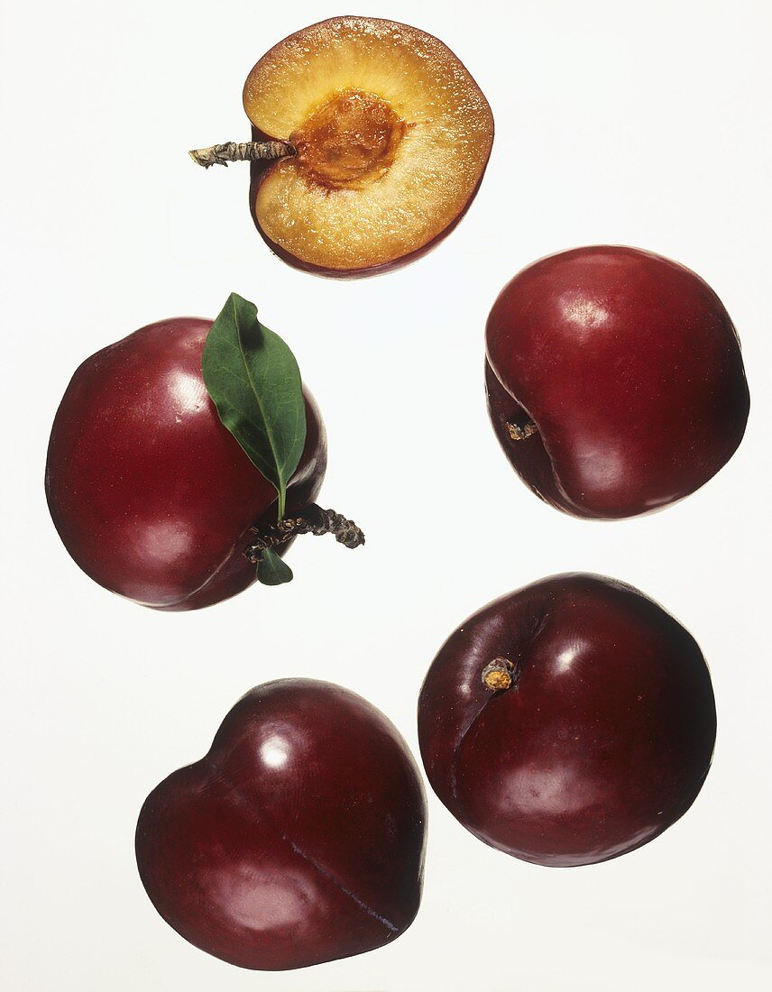 Four whole plums and half a plum against white background