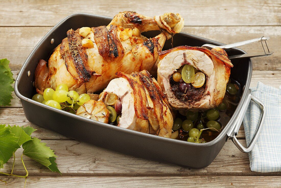 A chicken stuffed with grapes and raisins in a roasting tin
