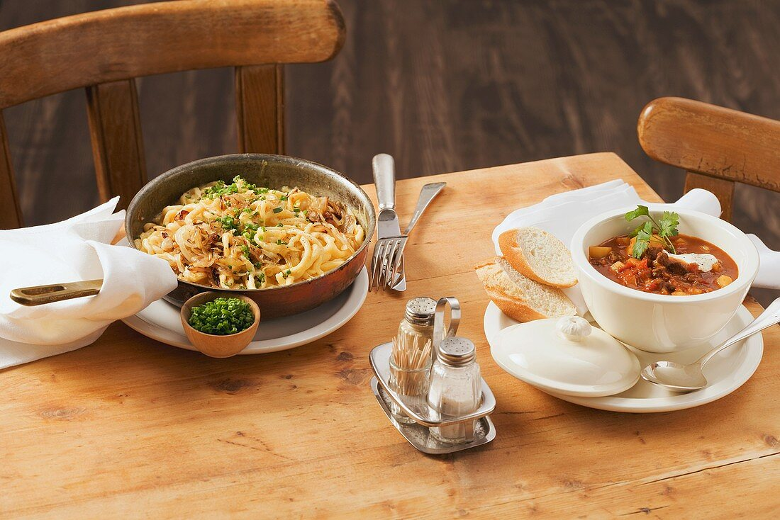 Cheese spätzle (soft egg noodles from Swabia) with fried onions and goulash soup
