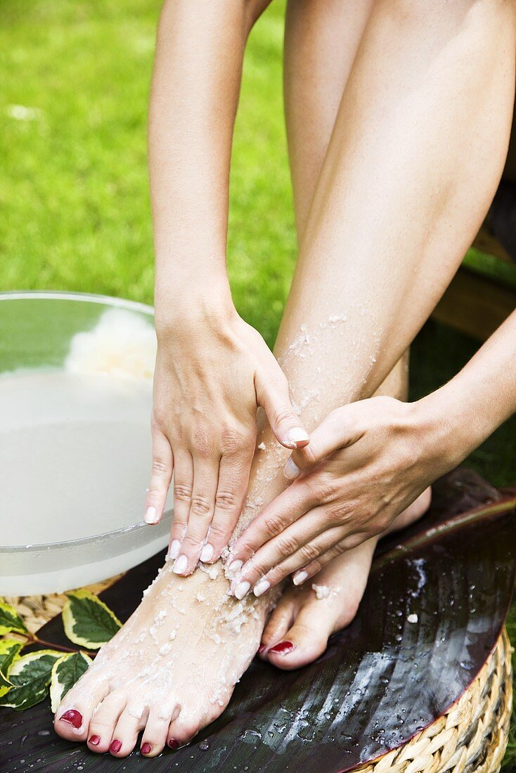 A woman giving herself a pedicure in a garden
