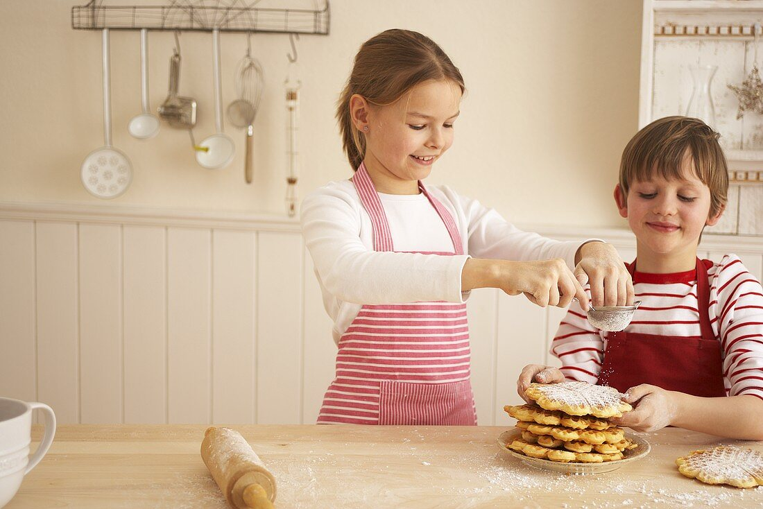 Two children baking waffles for advent