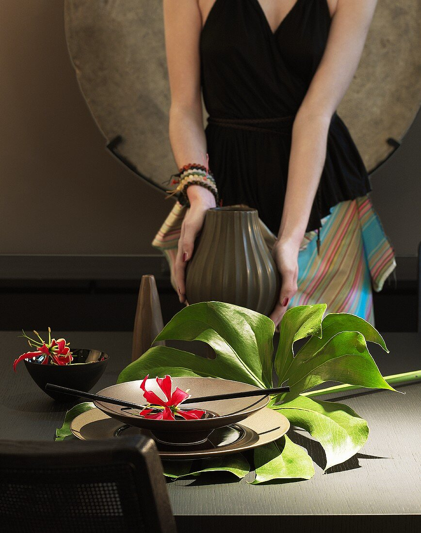 An illuminated flower in a bowl with a leaf and a woman in the background holding a vase