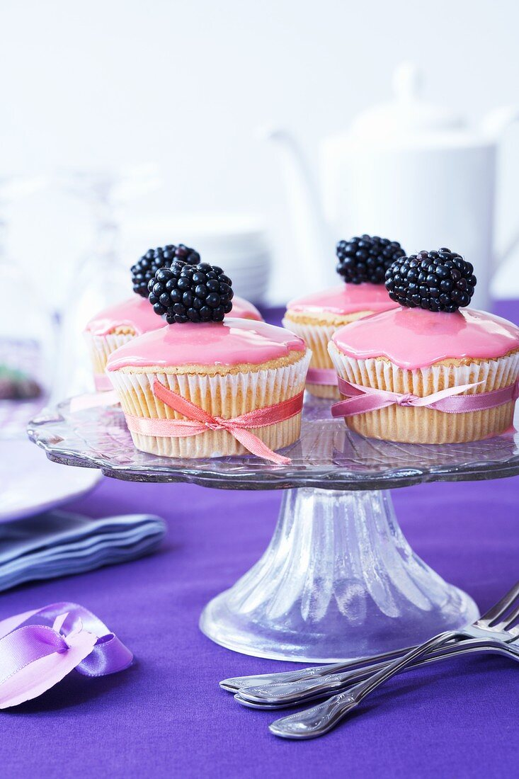 Muffins with pink sugar icing and blackberries
