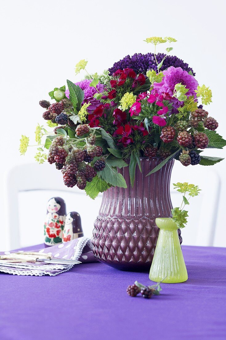 An autumnal bouquet in a purple vase