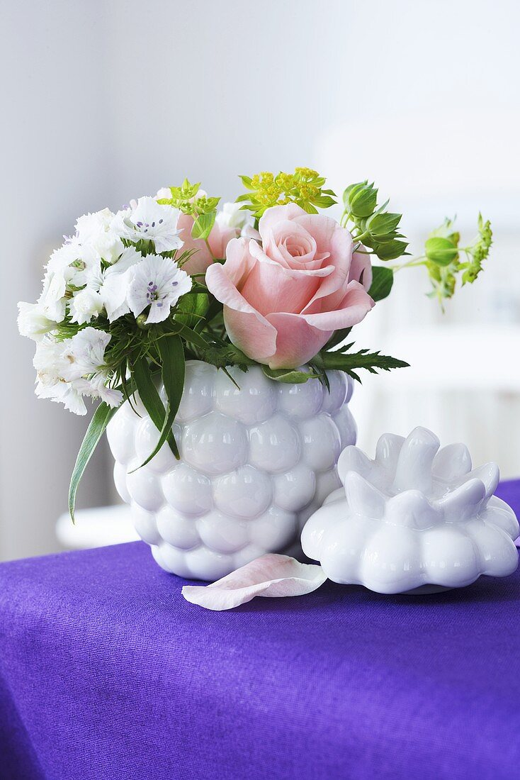 A berry-shaped jam jar being used as a vase