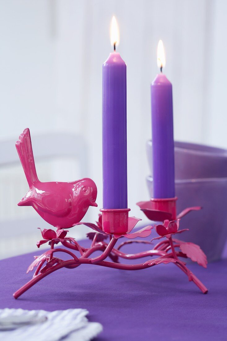 A bird candle holder with purple candles