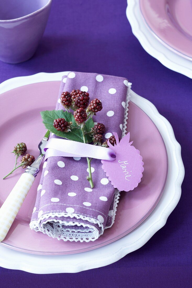 A place setting with a sprig of black berries